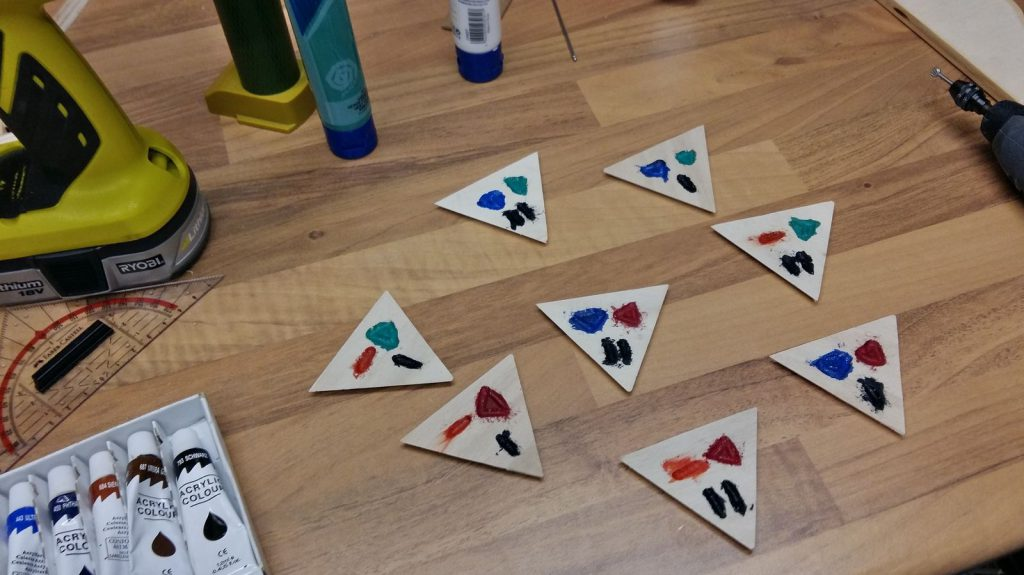 Triangles cut, symbols engraved and painted.