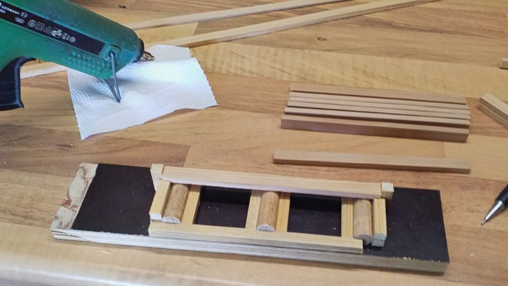 Spacers for the cross timbers are hot-glued in place.