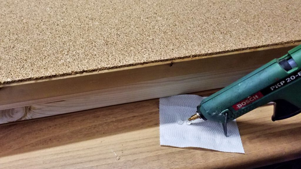 The cork mat's edges get an edge protector made from hot glue.